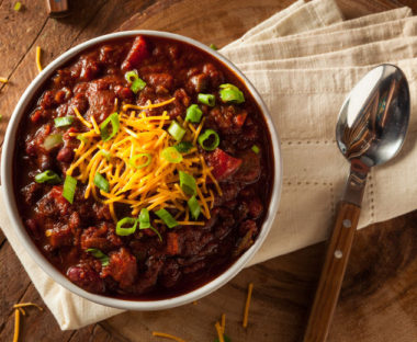 A bowl of chili on a rustic table.